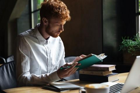 Rudowłosy młodzieniec przeglądający książkę i robiący notatki na leżącym przed nim notatniku i laptopie