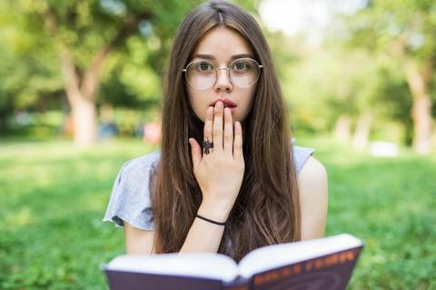 Dziewczyna w okularach i ciemnych włosach czytająca książkę na wolnym powietrzu na trawie, zasłania prawą ręką usta