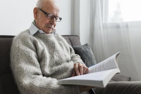 Starszy pan czyta książkę w pokoju na sofie