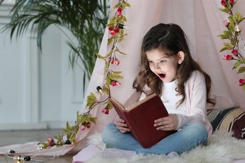 Ciemnowłosa dziewczynka czytająca książkę w domowym namiocie zrobionym z prześcieradła i ozdobionego girlandą kwiatów i lampkami