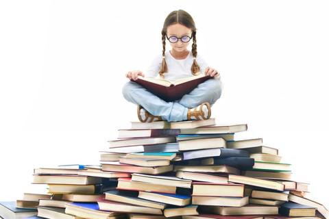 Dziewczynka w okularach czytająca książkę siedząc na stosie książek