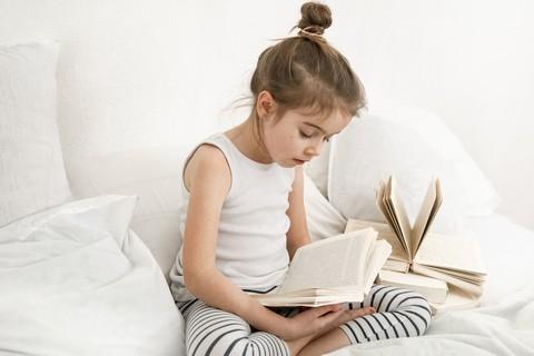 Mała dziewczynka czytająca książkę siedząc w łóżku