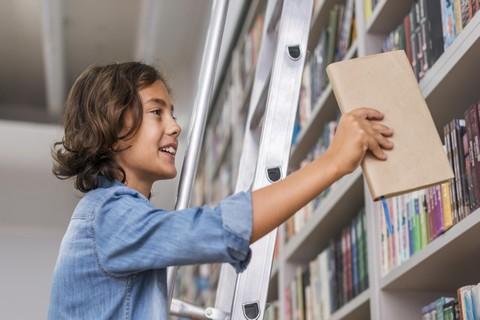 Dziecko odkładające książkę na półkę w bibliotece