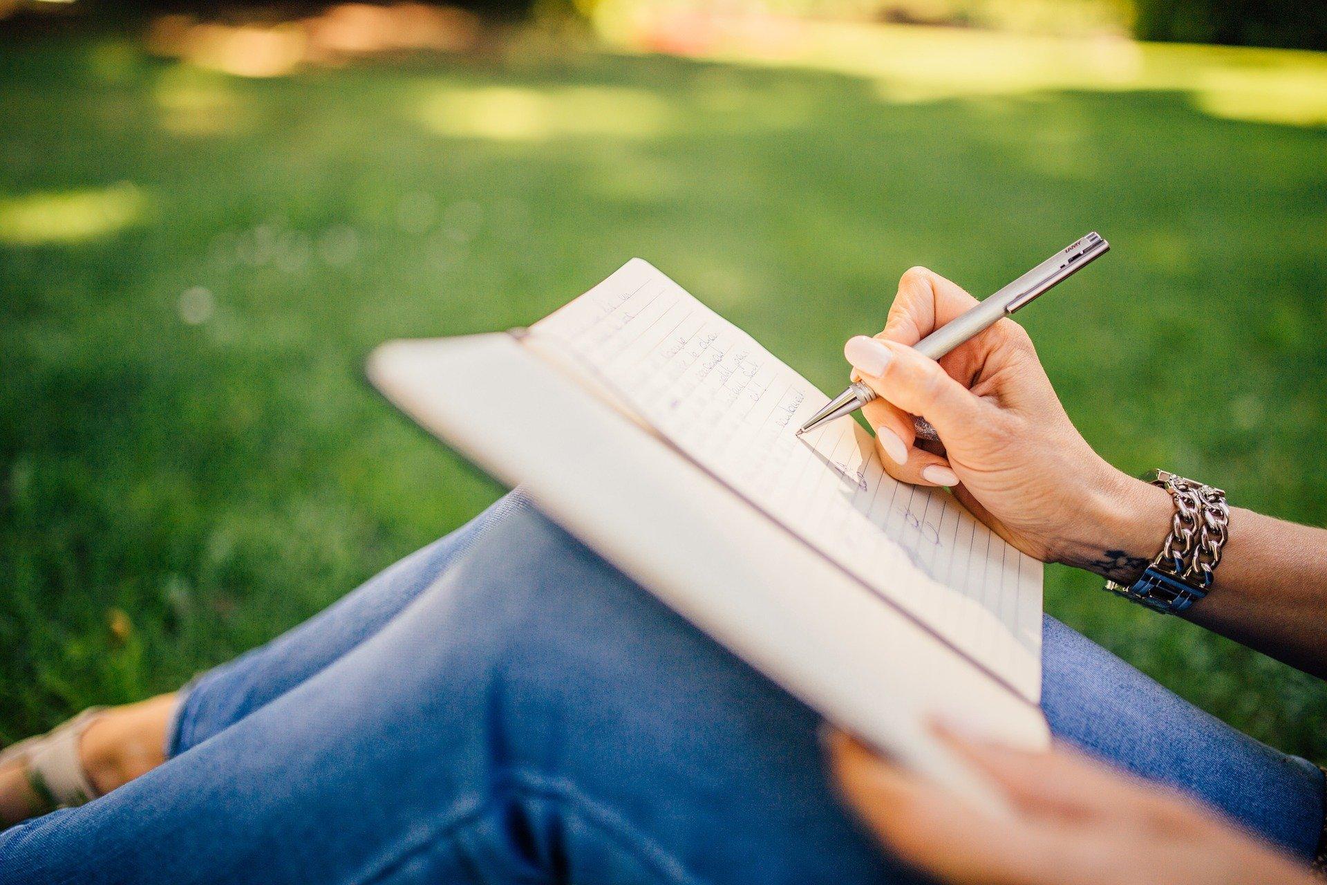 Pani siedząca na trawie pisze coś długopisem w notatniku. Image by StockSnap from Pixabay